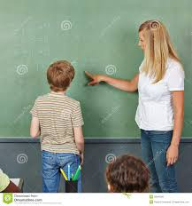 teacher helping child at chalkboard stock photo image  teacher helping child at chalkboard