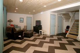 herringbone carpet tiles pattern in home living room interior design with wooden ceiling plus recessed lighting also dark brown leather accent chair plus carpet tiles home