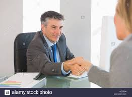 pleased businessman shaking the hand of a interviewee stock photo pleased businessman shaking the hand of a interviewee