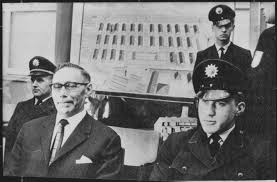west what is happening now main defendant wilhelm boger on the photo left awaits the beginning of the frankfurt auschwitz trial in 1964 in the background a map of the
