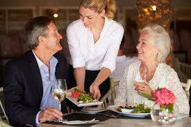 how to improve your customer service restaurant management waitress serving food to senior couple in restaurant
