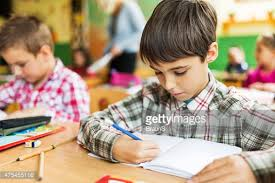 Elementary Student Writing During A Class In The Classroom Stock     Elementary student writing during a class in the classroom    Stock Photo