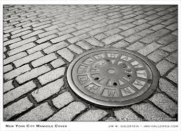 Cobbled area with a circular manhole. The cover has a spiderweb like design.