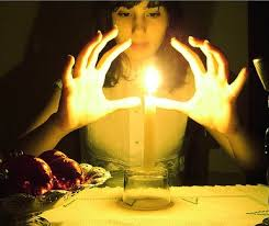 Young hands around lit candle
