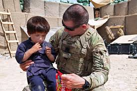 u s department of defense photo essay u s army staff sgt gregory lock offers candy to an afghan boy near forward operating