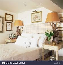 white cottage bedroom stock photo white pillows against checked headboard on bed in small co