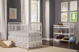 slate grey walls stand over dark hardwood flooring with beige rug in this nursery featuring white baby nursery yellow grey gender neutral