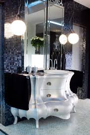 this custom vanity makes a statement that is masculine yet sensual walls and floors are one inch glass tiles with bold lighting ample mirrors and a ample shower lighting