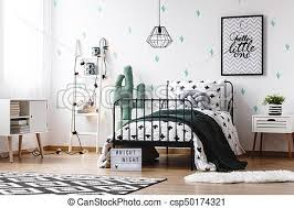 Black blanket on kid's <b>bed</b>. <b>Toy</b> in <b>shape</b> of <b>cactus</b> next to <b>bed</b> with ...
