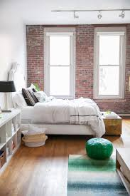 a bright bedroom with exposed brick walls and white bedding bedroomterrific eames inspired tan brown leather short