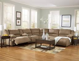 warm light blue wall paint color scheme of apartment living room design with brown fabric sectional recliners sofa and brown varnishes rectangle oak wood brown fabric lighting