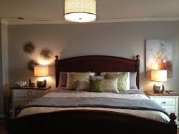 gorgeous bedroom idea with brown wooden bed frame designed with headboard and green pillows also blue white blanket combine with warning side table lamps bedroom bedroom ceiling lighting ideas choosing