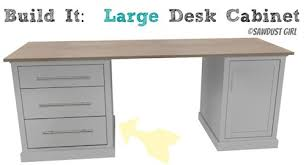 note how table legs are attached to one end of the desk while cube shelving adds support to the opposite end and middle building office desk