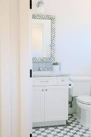bathroom features gray shaker vanity: white and gray bathroom features a west elm parsons wall mirror gray herringbone placed above a white shaker vanity topped with carrera marble alongside a