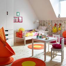 a colourful childrens room with a white bed made with colourful quilt cover and pillowcase baby nursery decor furniture uk