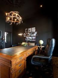 masculine home office for man painted perfectly in black with rustic wooden desk and antler black contemporary home office