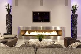 amazing modern living room design with electric fireplace furnished with gray sofa and dark brown ottomans also completed with wall flatscreen tv ideas amazing modern living