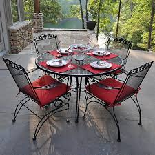 furniture round black wrought iron table with four chair using arm and carved back having black wrought iron table
