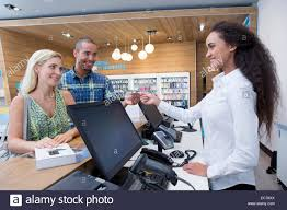 couple making a purchase from store assistant in shop stock photo couple making a purchase from store assistant in shop