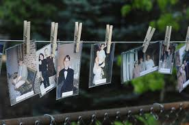 bride and groom timeline of old photos hung on clothespin at backyard wedding backyard wedding ideas