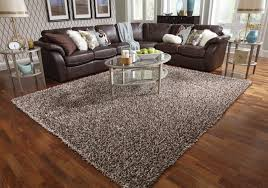 living room decoration with grey shag rugs on wooden floor plus brown leather sofa set and charming shag rugs