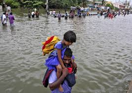 flooding in southeastern disrupts power flights pbs newshour a man carries a girl through flooded streets in chennai on dec
