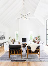 bright white and spacious living room with modern light fixture leather armchairs casual living room lots