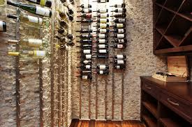 brick wall home wine cellar design ideas with horizontal hanging wine bottles on iron hooks barrel wine cellar designs