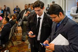 ramping up for opening usc village recruits local right check their smart phones as they wait for their interview during usc job fair for full time positions in retail hospitality customer service
