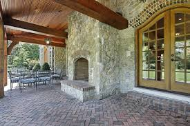 outdoor fireplace paver patio: beautiful covered patio with red brick pavers and rustic outdoor stone fireplace