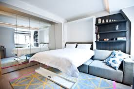 city studio apartment small trendy master bedroom photo in london with gray walls and medium tone bedroom furniture solutions