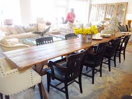 long farmhouse dining table made from reclaimed wood with flower centerpieces and 8 black wooden dining chairs and 2 white fabric cover dining chairs black wood dining room