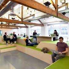 an indoor village green bleacher style seating and a reception desk modelled on a airbnb cool office design train tracks