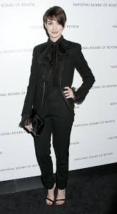 8 ways to wear the pant suit anne hathaway dons a saint laurent tuxedo pant suit in black ruffled shirt photo