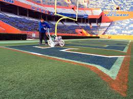 florida s grass guy cutting through the competition wuft news jason smith turf coordinator rolls the first coat of white paint on the florida logo
