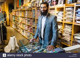 shop assistant clothes stock photos shop assistant clothes stock portrait of tailor behind counter in men s clothes shop stock image