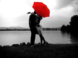 couple embrace under a red umbrella
