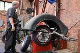 authentic muscle car tires motor news technician mounting new tire on rim technician spin balancing new tire