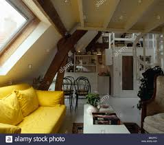 bright yellow sofa below velux window in openplan attic living room and kitchen in traditional apartment bright yellow sofa living