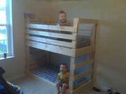 bedroom brown wooden homemade bunk beds with brown wooden board railing and patterned blue bedsheet children bunk beds safety