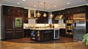the large island with schoolhouse pendant lights rich dark cabinets and light granite countertops combine cabinet and lighting