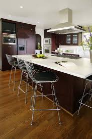 kitchen island granite top sun: high contrast look in this kitchen courtesy of dark stained cabinetry white countertops
