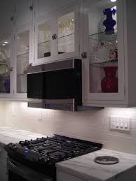 picture of glass front kitchen cabinets with decorative puck lights inside cabinet lighting puck light