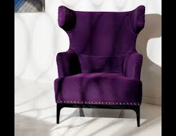 purple velvet upholstered wingback chair with silver nails accent and black stained wooden legs placed on ceramic purple black white