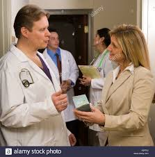 busy doctor meets pharma rep sw in the halway stock busy doctor meets pharma rep sw in the halway