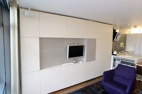 huge fitted sleek wall unit with clever use of storage and hidden desk painted finish with fabric paneling behind stunning riverside apartment bespoke wall storage