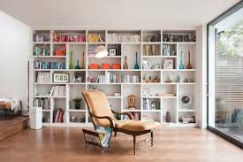 portfolio example of a trendy open concept living room design in london with a library and bespoke wall storage