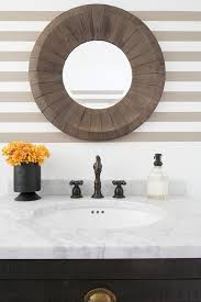 washstand bathroom pine: a round salvaged wood mirror is mounted on a beige striped wall above a black pine washstand fitted with distressed brass cup pulls and a carrera marble