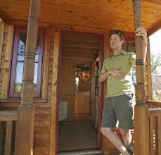 jay shafer owner of tumbleweed tiny houses is seen on the front porch of a boulder tiny house front