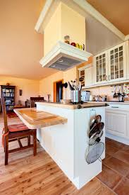 traditional kitchen islands provide lots this compact island in white features two tiered natural wood countert